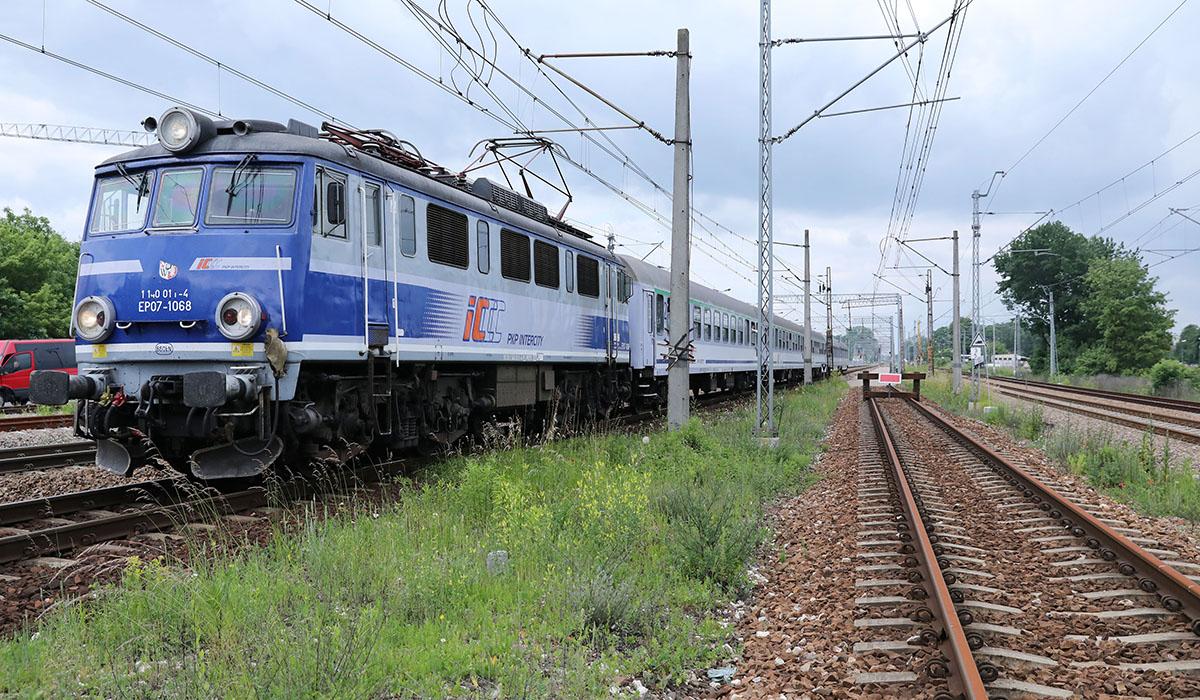 Na zdjęciu widoczny jest pociąg przejeżdżają przez tory kolejowe.