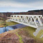 Wizualizacja przedstawia dwa zdjęcia, które przesuwa się przy pomocy suwaka. Jedno zdjęcie pokazuje most na Drawie przed modernizacją, a drugie zdjęcie to wizualizacja jak docelowo most będzie wyglądał po modernizacji.
