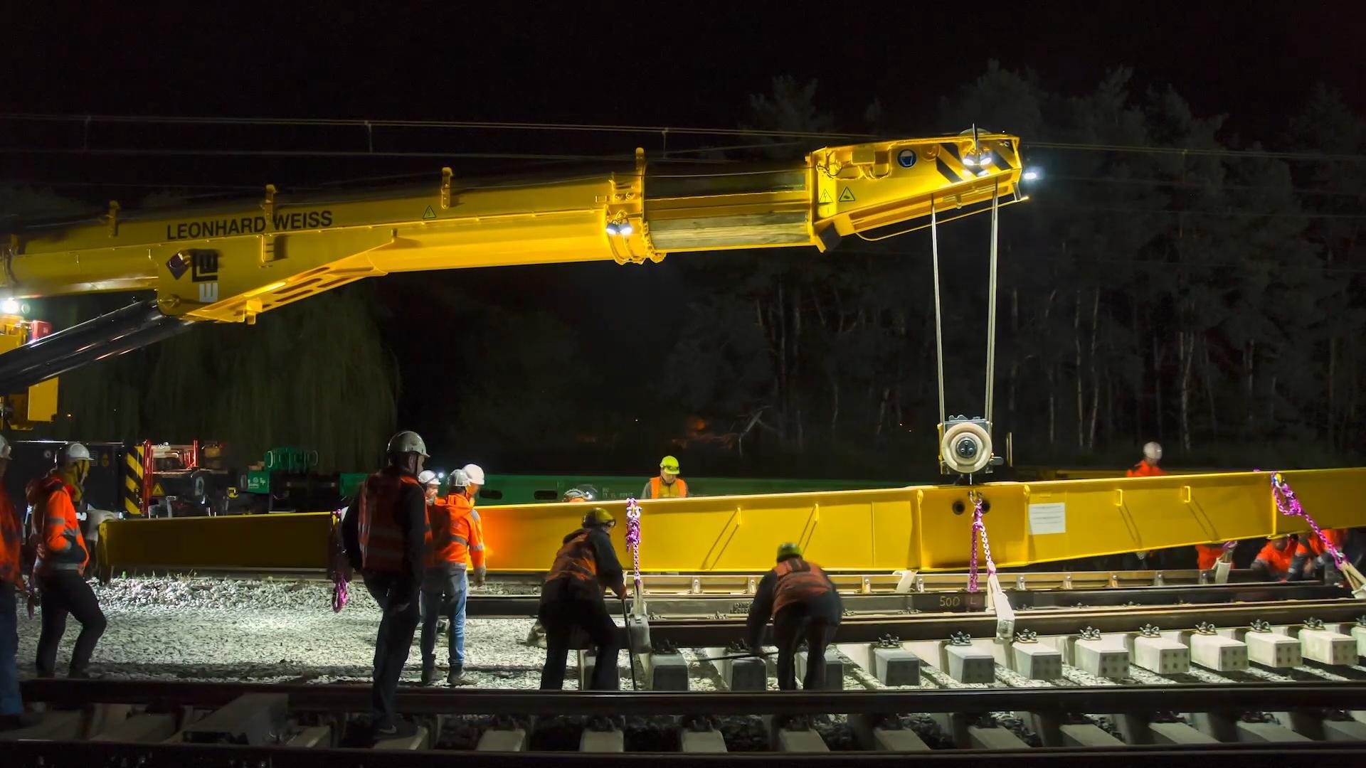 Zdjęcie przedstawia nocny montaż rozjazdów przy użyciu specjalnej platformy na stacji Szamotuły.