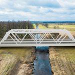 Wizualizacja przedstawia dwa zdjęcia, które przesuwa się przy pomocy suwaka. Jedno zdjęcie pokazuje most na Bukówce przed modernizacją, a drugie zdjęcie to wizualizacja jak docelowo most będzie wyglądał po modernizacji.