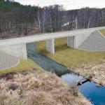 Wizualizacja przedstawia dwa zdjęcia, które przesuwa się przy pomocy suwaka. Jedno zdjęcie pokazuje most na Mierzęckiej Strudze przed modernizacją, a drugie zdjęcie to wizualizacja jak docelowo most będzie wyglądał po modernizacji.