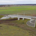 Wizualizacja przedstawia dwa zdjęcia, które przesuwa się przy pomocy suwaka. Jedno zdjęcie pokazuje wiadukt kolejowy w Krzyżu Wielkopolskim przed modernizacją, a drugie zdjęcie to wizualizacja jak docelowo wiadukt będzie wyglądał po modernizacji.
