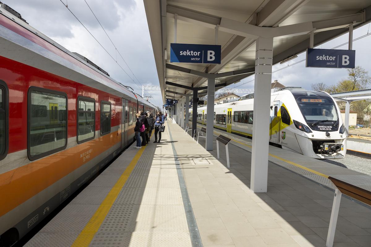 Zdjęcia przedstawiają gotowy peron, na którym poruszają się pasażerowie, prace na stacji oraz modernizacje przejazdów kolejowo-drogowych w Szamotułach.