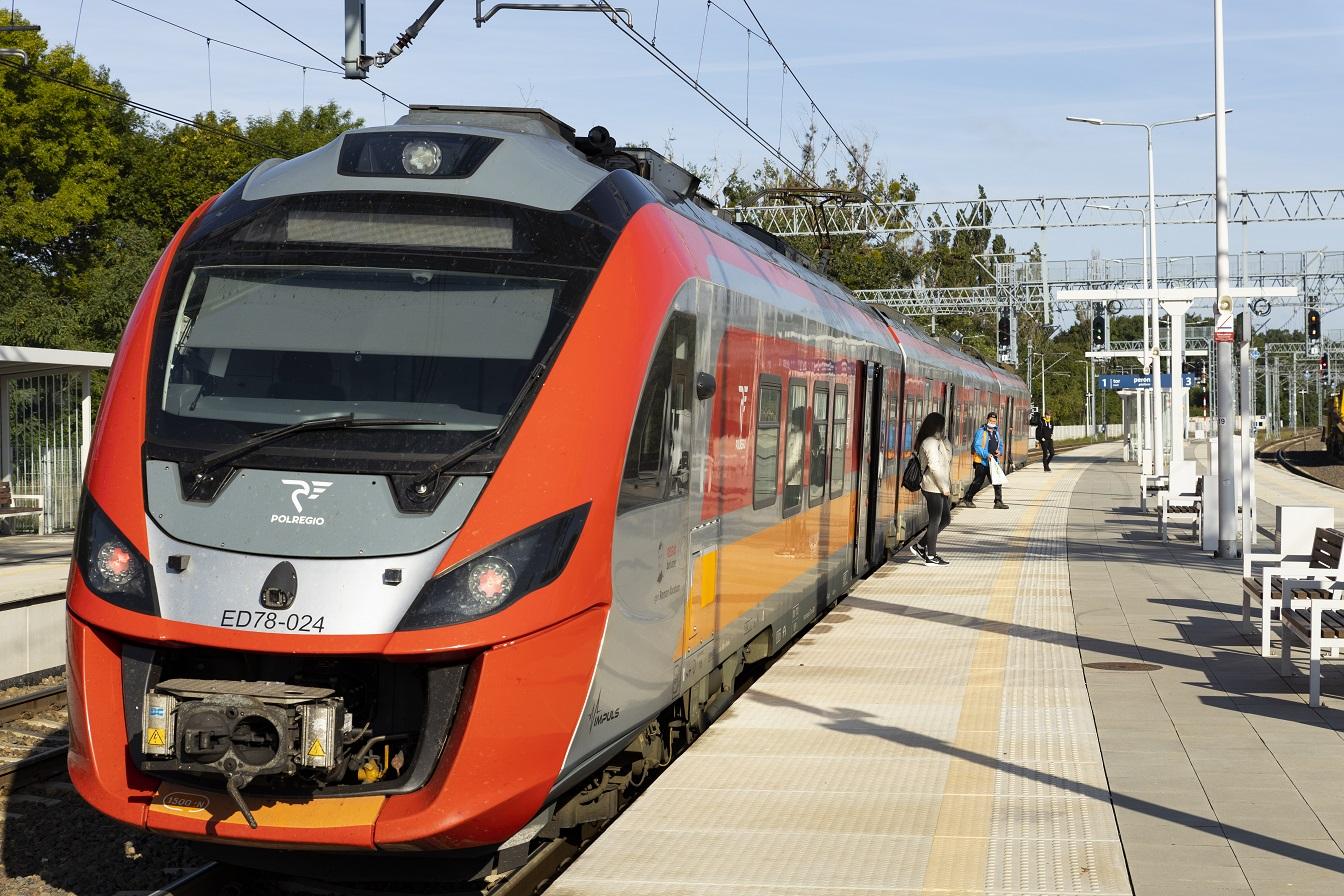 Na zdjęciu widoczny jest pociąg, który stoi na stacji Kiekrz. Z pociągu wysiadają pasażerowie.