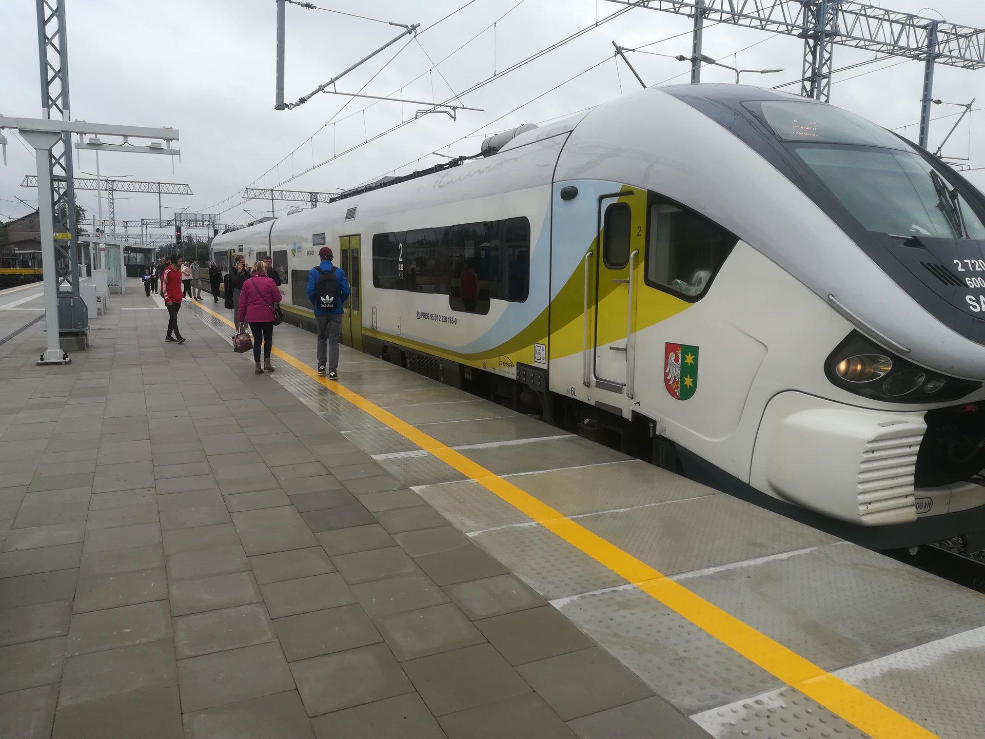 Na zdjęciu widać pasażerów wsiadających do pociągu z nowo otwartego peronu na stacji Rokietnica.